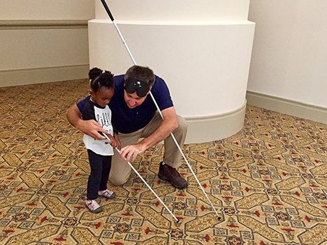 Little girl getting cane travel lesson
